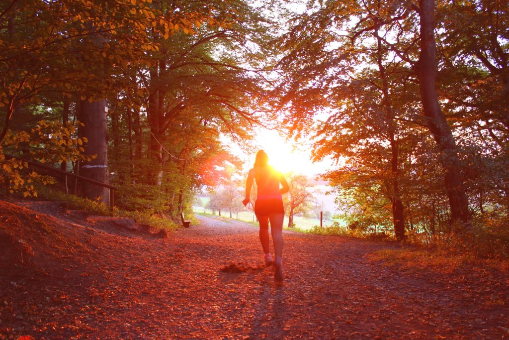 Woman racing through autumn forest into the sun